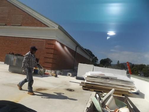 LEAKS NO MORE? Roofers work on repairing the leaky roof at Sevier Middle School. KCS is spending nearly $600,000 to end years of water damage at Sevier.