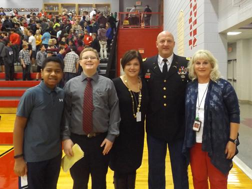 WRAPPING IT ALL UP. The organizers and presenters, including student council president Marcus, host Gabriel, Sevier principal Holly Flora, veteran Alan Bagley and Family Liaison Marty Meade, pose for a photo to wrap up the Veterans Day celebration.