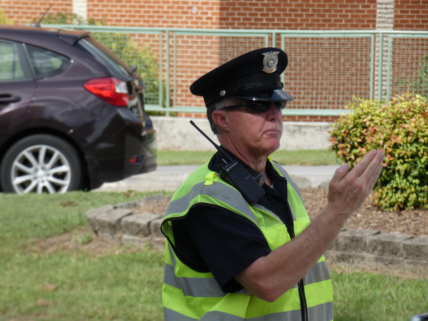 SAFETY FIRST. Student Resource Officer Mike Campbell directs traffic before school starts. The SRO position is one of several ways the school system works to keep students safe.