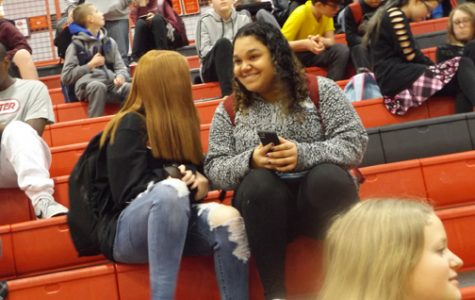 ENJOYING THE MUSIC. Many students use their devices and listen to music in the gym before school starts. Most would like to be able to do so in class, too.