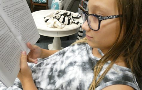 READING WITHOUT MUSIC. Sixth grade student Cassandra reads a book in the school library. Teachers argue that students cannot focus on their reading and classwork if they are listening to music.