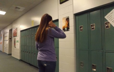 HELP IS AVAILABLE. Macy Davis, left, checks out a poster advertising the new